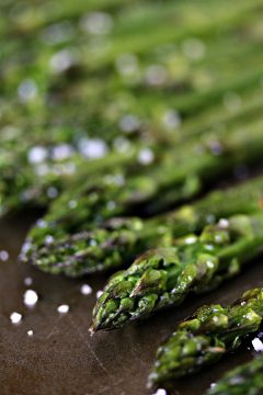 Roasted Asparagus with Lemon, Garlic and Shallot Butter on a cookie sheet with salt sprinkled over top of it.
