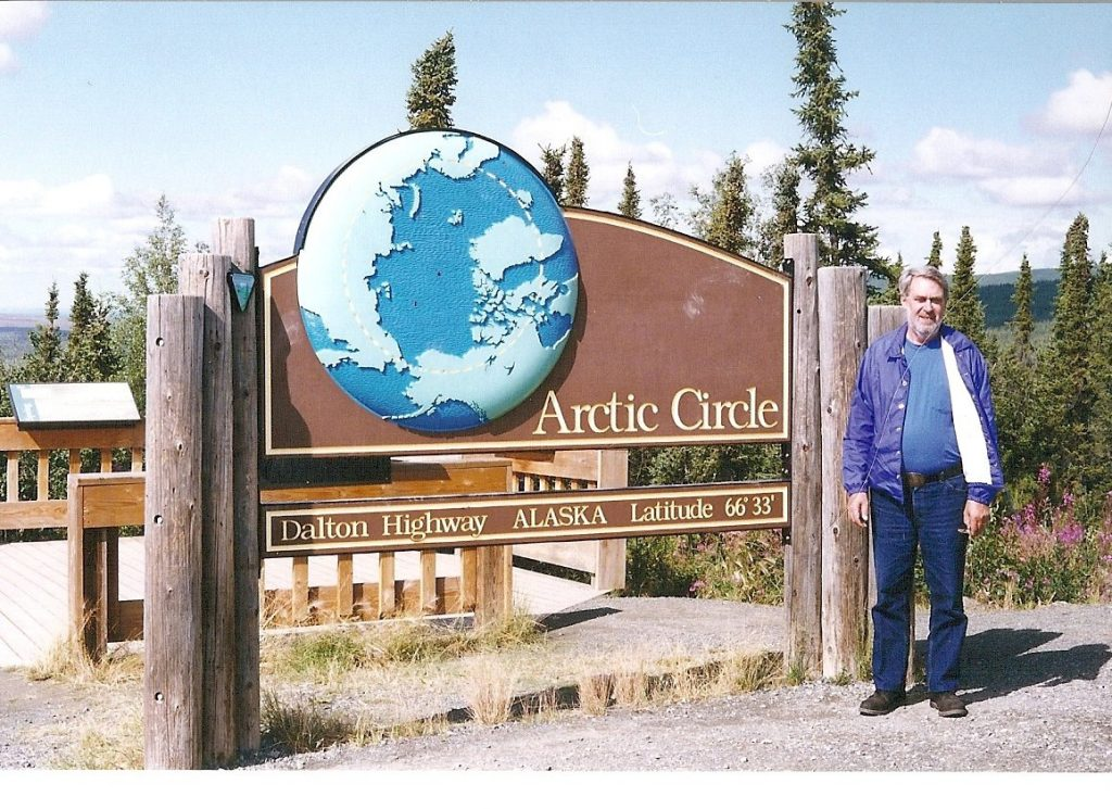 Dad standing by a sign for the Arctic Circle