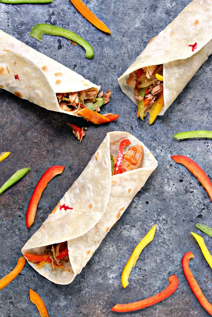 chicken fajitas on a grey counter with cut up peppers scattered around