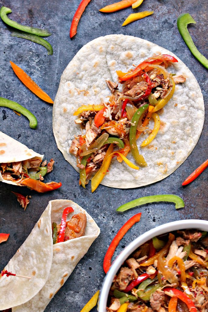 chicken fajitas on a grey table, some are folded over ready to be eaten, one is open faced, and there's a white bowl with the fajitas inside, peppers are scattered around randomly
