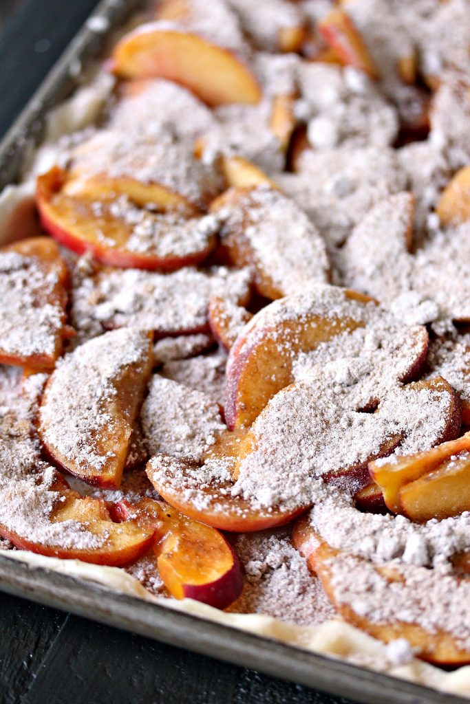 Prepping the peaches by sprinkling with sugar before baking a Rustic Peach Slab Pie