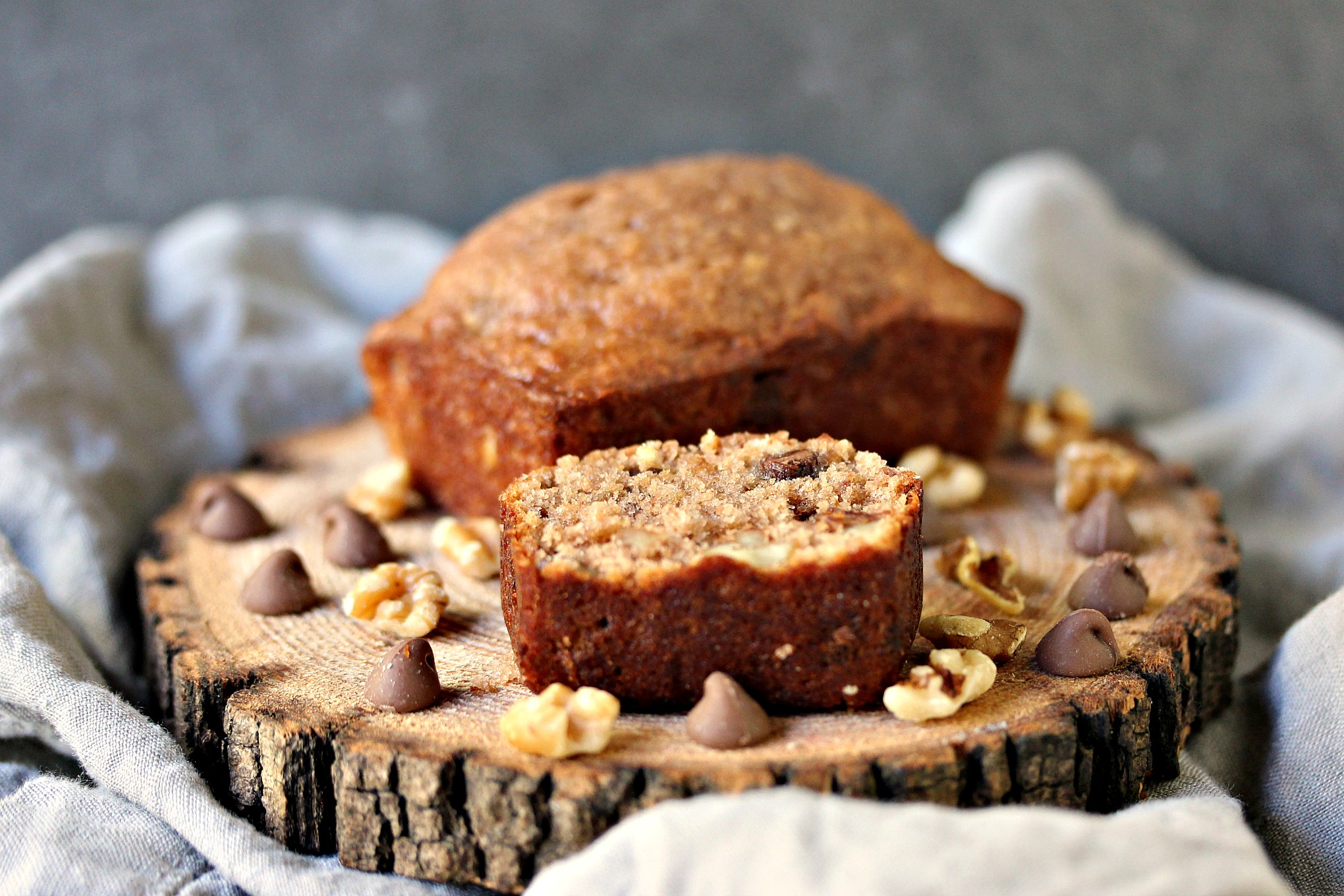 loaf and slice of Peanut Butter Chocolate Banana Bread with Walnuts on a wood trivet on a grey napkin