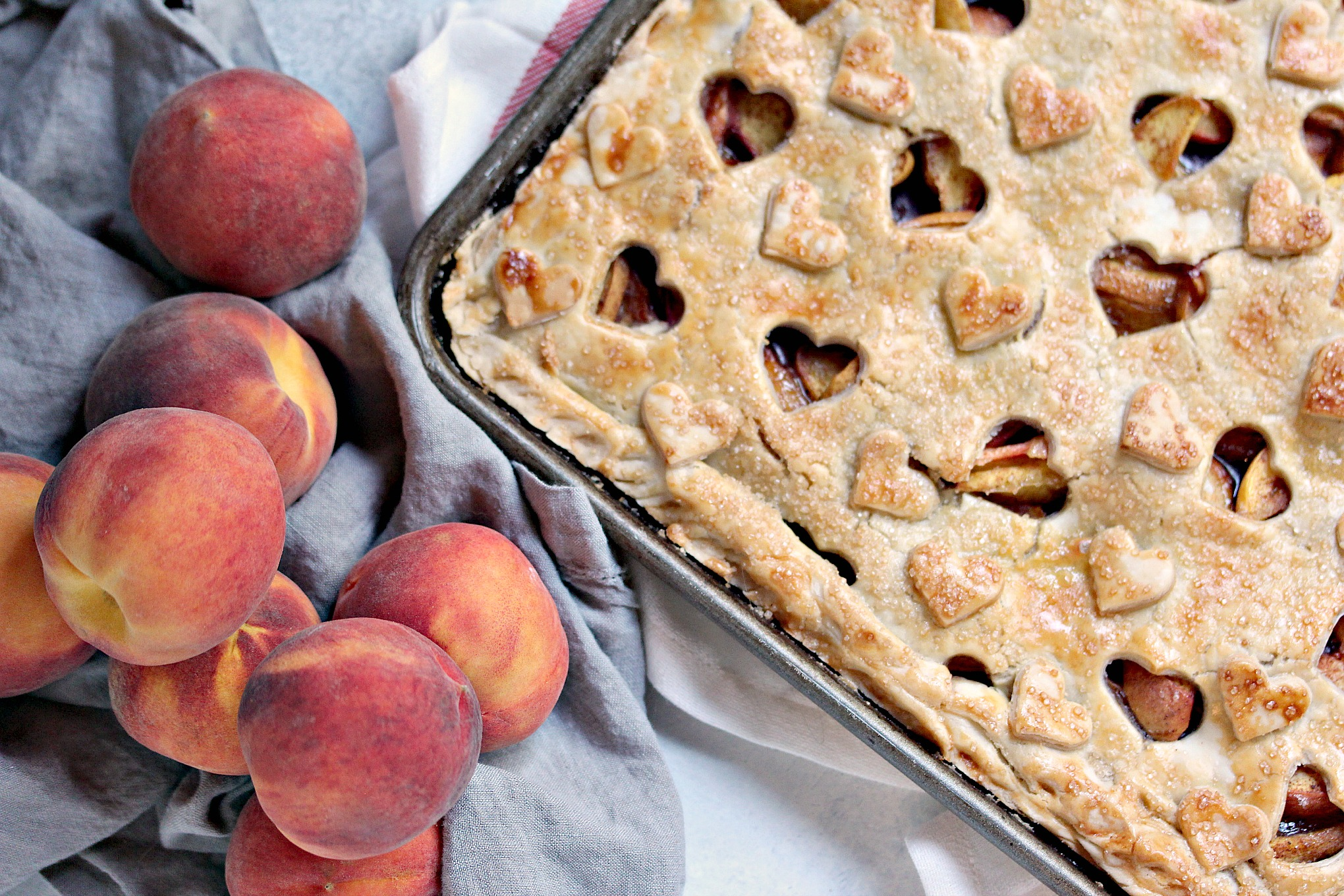 peaches on a table with a baked Rustic Peach Slab Pie next to it
