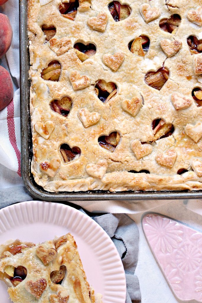 overhead image of a rustic peach slab pie baked in a cookie sheet with a slice of pie on a plate nearby