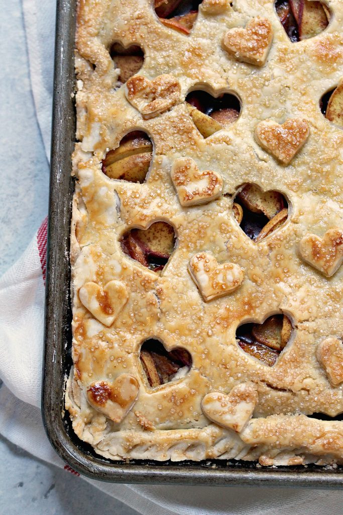 close up overhead image of rustic peach slab pie baked in a cookie sheet