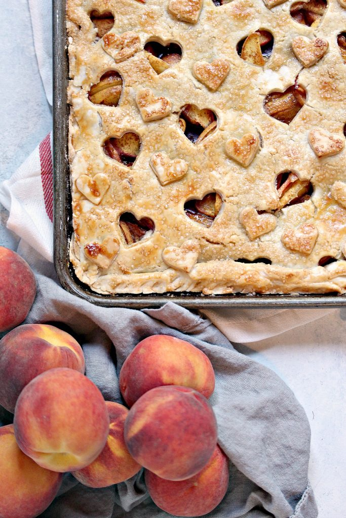 baked Rustic Peach Slab Pie on a table with a bowl of peaches nearby