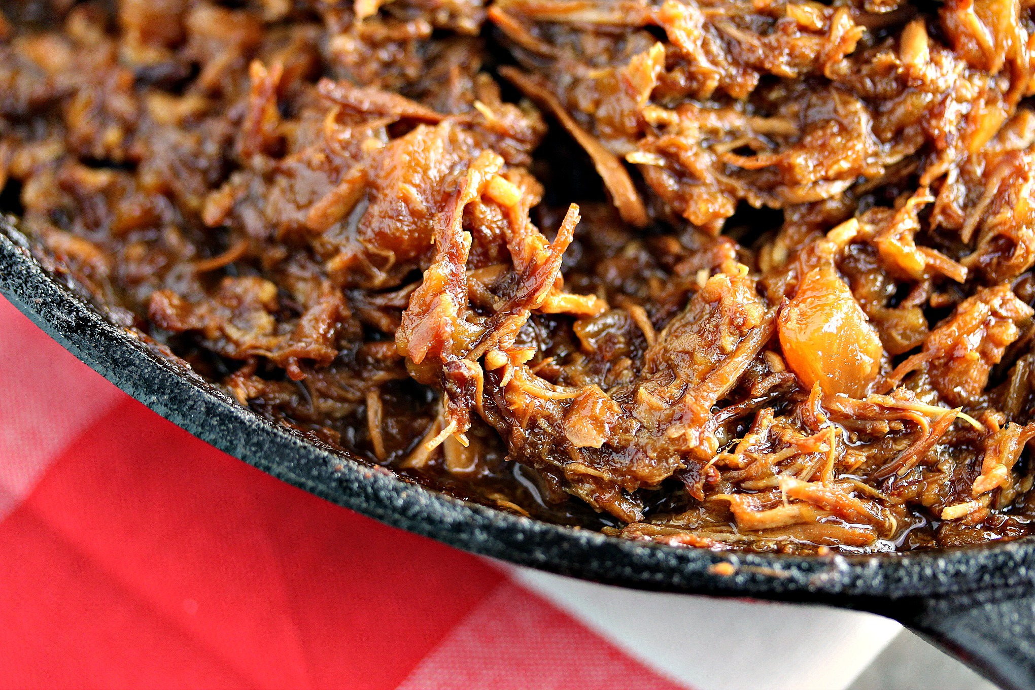 close up image of Slow Cooker Huli Huli Chicken in a black cast iron skillet sitting on a red and white napkin