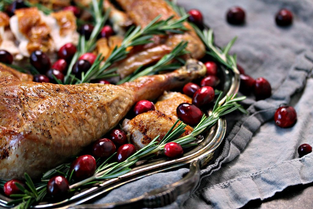 Spatchcock turkey sliced and served on a silver tray with herbs and cranberries.