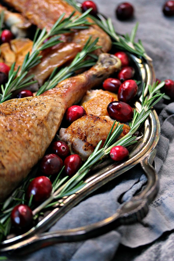 Spatchcock Turkey sliced and presented on a silver tray with herbs and cranberries for decoration.