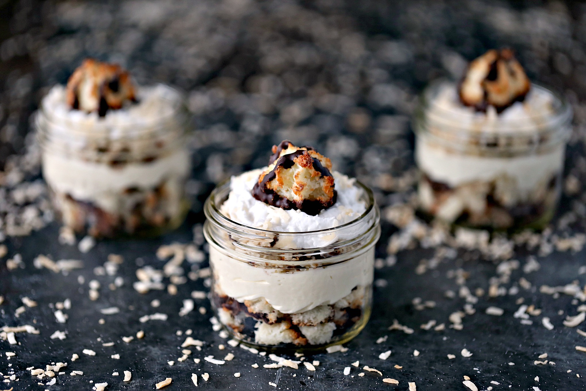 Coconut Macaroon Cheesecake Parfaits from cravingsofalunatic.com- Layers of coconut macaroons, coconut cheesecake filling, toasted coconut, and coconut whipped cream. All topped off with a coconut macaroon cookie! @CravingsLunatic