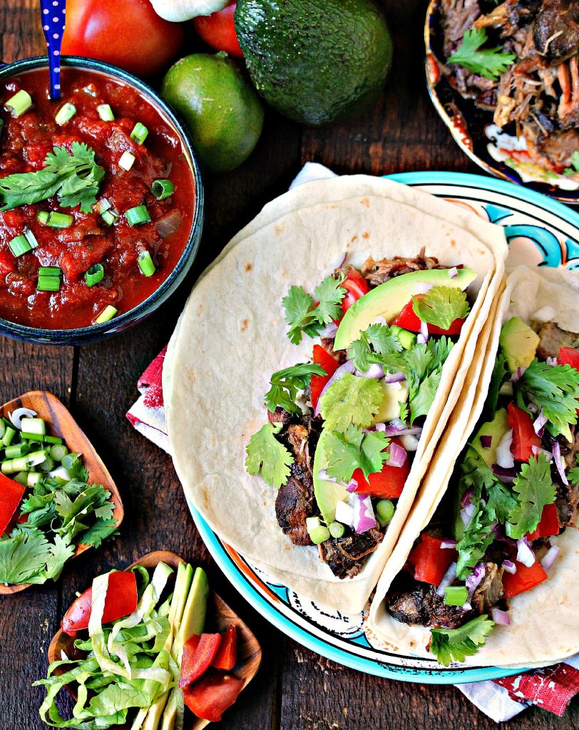 Sweet and Spicy Slow Cooker Carnitas served on tortillas with ingredients scattered around.