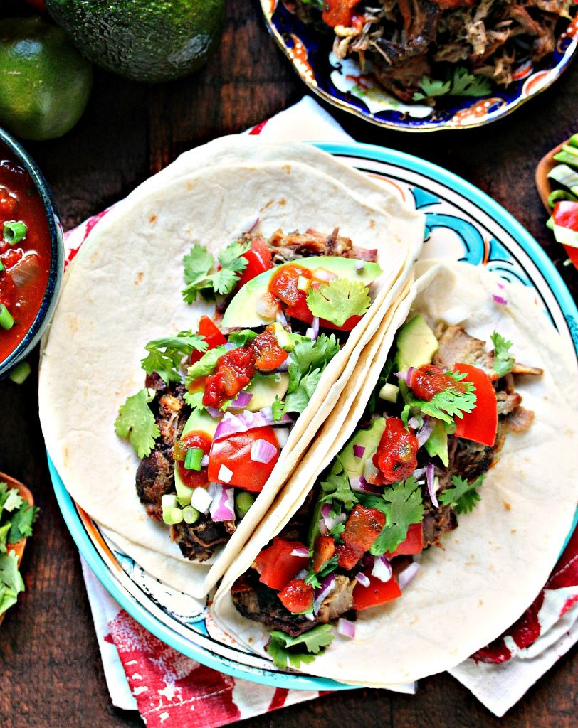Sweet and Spicy Slow Cooker Carnitas piled on tortillas with ingredients scattered around.