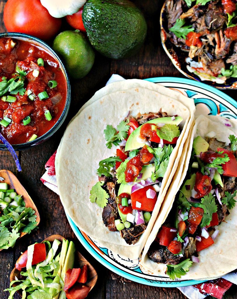 Sweet and Spicy Slow Cooker Carnitas piled on tortillas with all the extra ingredients scattered around.