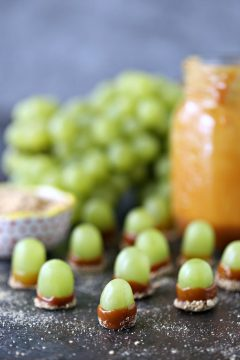Green grapes dipped in melted caramel and graham crumbs.