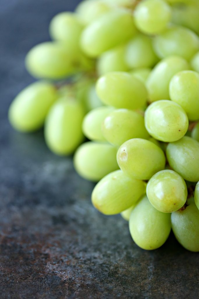 Bunch of green grapes on a dark surface
