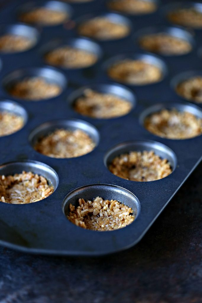Granola cups pressed into a mini muffin tin ready to be baked in the oven.