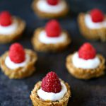 Granola cups stuffed with yogurt and berries sitting on a dark counter.