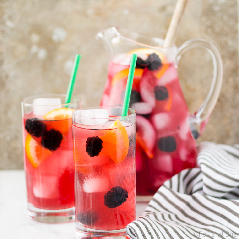 Berry Sangria Iced Tea from Fox and Briar in a glass pitcher and two tall glasses on a counter with a towel nearby
