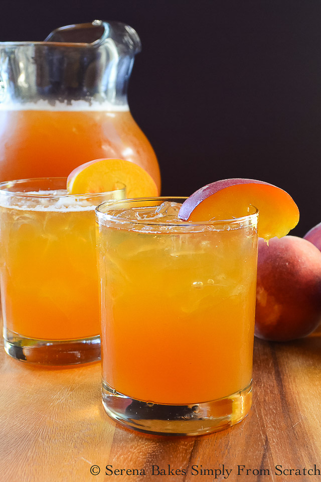 Peach Whiskey Iced Tea from Serena Bakes Simply from Scratch in a pitcher and two glasses garnished with sliced peaches