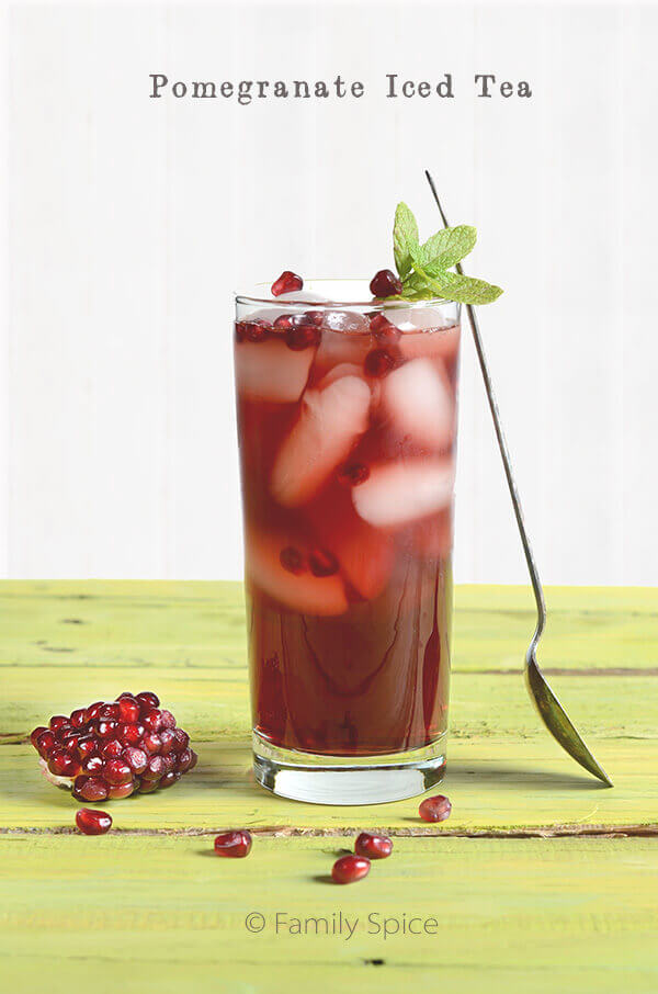 Pomegranate Iced Tea made by Family Spice in a tall glass with a spoon resting up against it