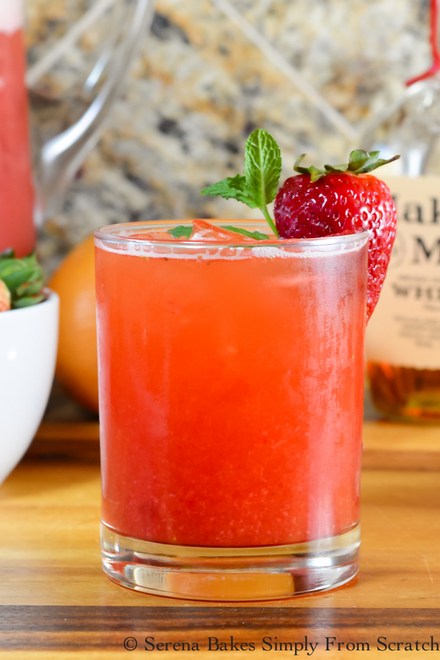 Strawberry Grapefruit Whiskey Iced Tea from Serena Bakes Simply from Scratch in a glass filled to the brim and garnished with a strawberry and fresh herbs