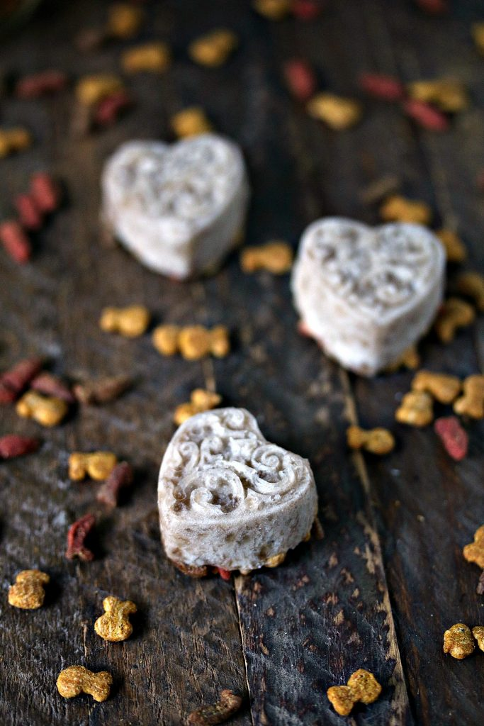 Cat friendly frozen banana bites shaped like hearts on a wood board with tiny cat treats scattered about.