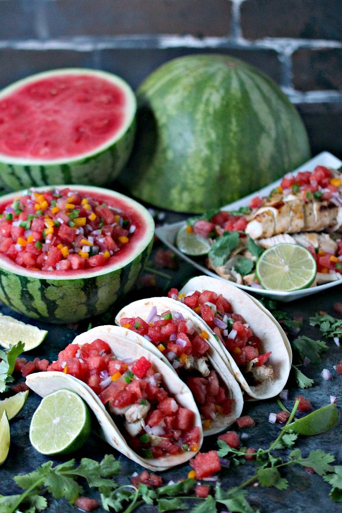 Grilled honey lime chicken tacos ready to be served with watermelon salsa in a hollowed out watermelon half and cut wateremelons and ingredients scattered randomly.