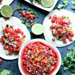 Overhead image of grilled honey lime chicken tacos with watermelon salsa. Watermelon salsa is served in a hollowed out watermelon half. Chicken is on a white plate. Everything is spread out on a greyish blue board.