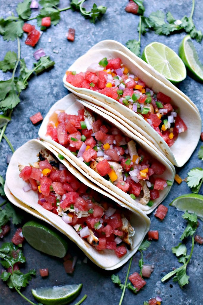 Overhead image of 3 grilled honey lime chicken tacos with watermelon salsa, ingredients are scattered around a dark surface randomly.