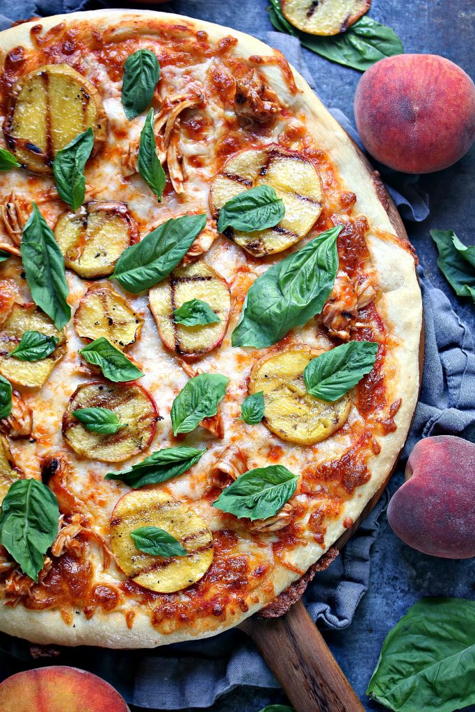 grilled peach and chicken pizza with fresh basil on a wood board with grey napkin underneath. full and slices peaches and basil are scattered around the pizza on a dark counter.