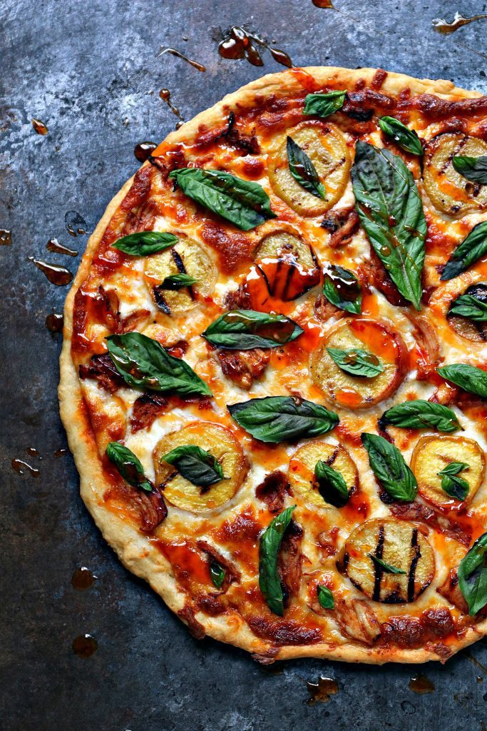 overhead image of a cooked pizza that is topped with grilled peaches, chicken and basil