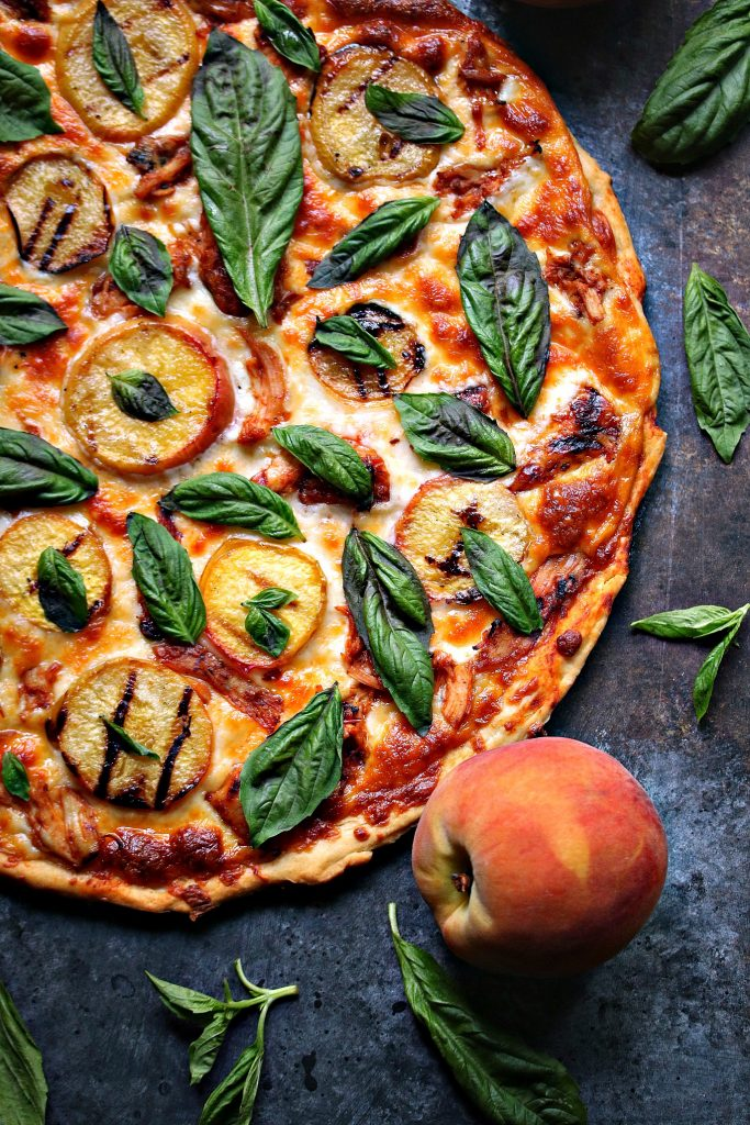 Grilled Peach and Chicken Pizza with Fresh Basil from cravingsofalunatic.com- This recipe takes the smokiness of grilled chicken and the sweetness of grilled peaches and combines them in a perfectly grilled pizza. Fresh basil takes it to the next level.