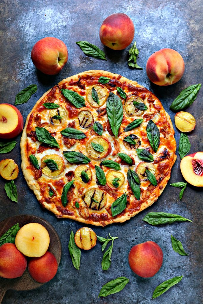 overhead image of a grilled peach and chicken pizza with fresh basil, full peaches, sliced peaches and basil are scattered around the pizza on a dark counter