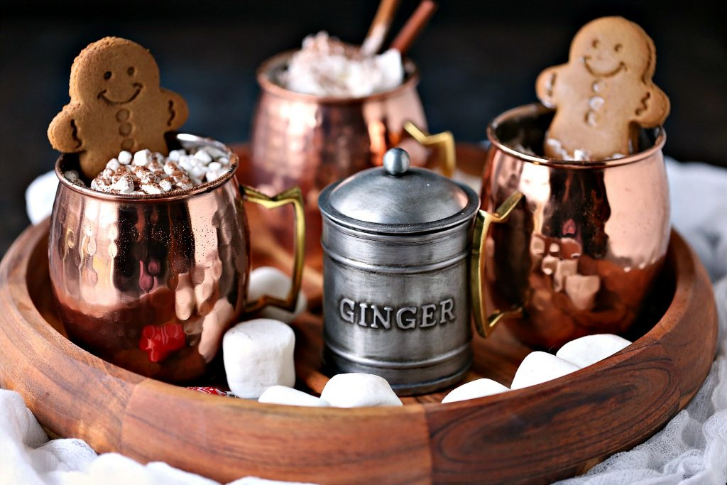 Gingerbread hot chocolate served on a tray with mugs filled with extra marshmallows and gingerbread cookies.