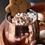Gingerbread hot chocolate with added mini marshmallows and a gingerbread cookie.