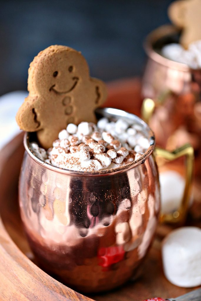 Gingerbread hot chocolate served in mugs with lots of marshmallows and a gingerbread cookie!