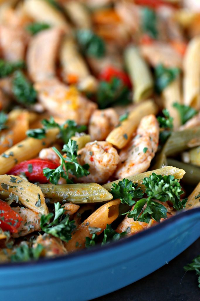 Close up photo of cooked chicken and vegetable pasta in a blue skillet garnished with parsley.