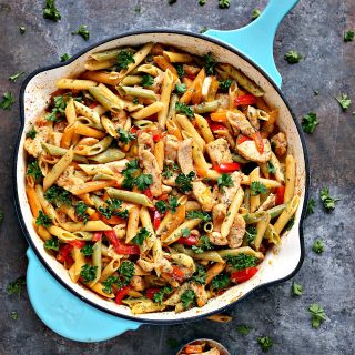 Chicken and vegetable pasta in a blue skillet with a spoonful of food sitting beside it on a counter.