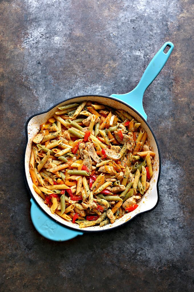 Overhead view of chicken and vegetable pasta in a large blue skillet sitting on a counter.