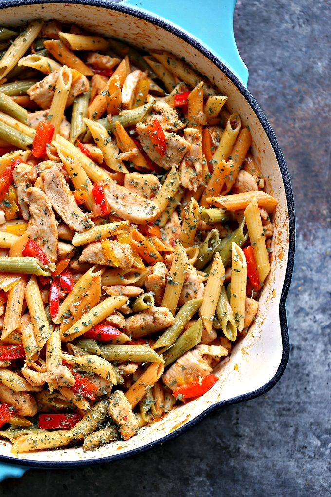 Close up photo of chicken and vegetable pasta in a blue cast iron skillet.