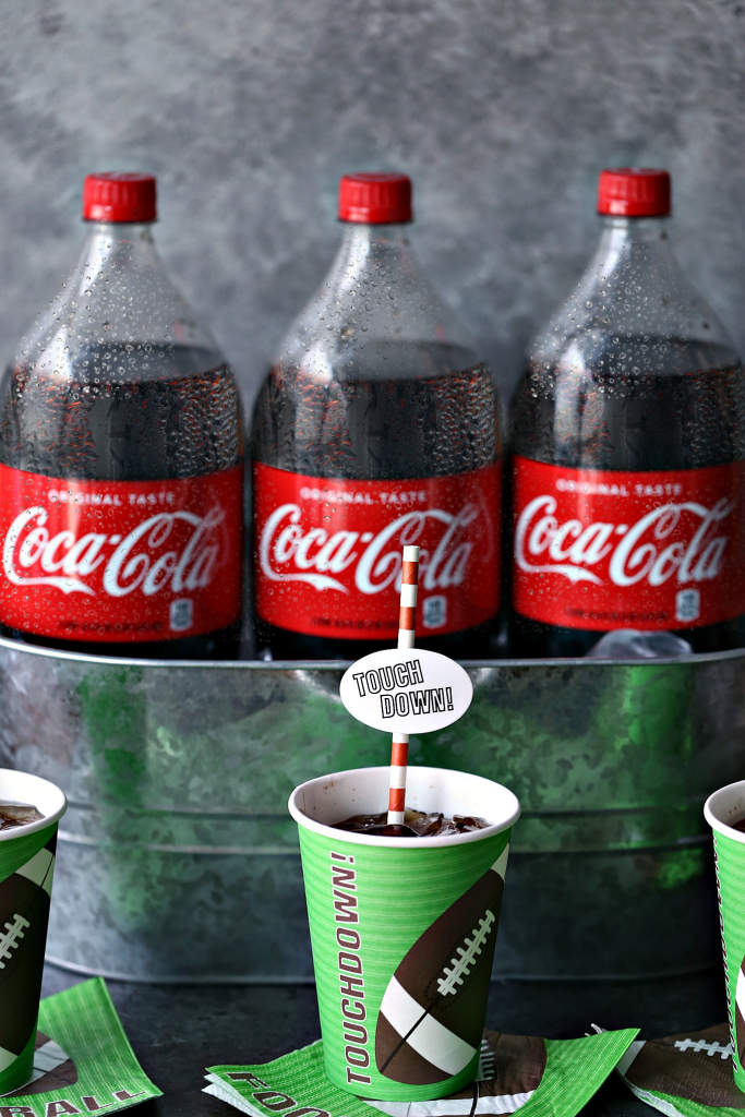 Coca cola bottles in a metal basket with glasses of coke nearby with straws in them.