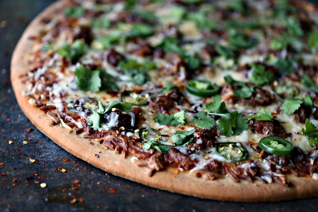Pressure cooker pulled pork piled on top of pizza sitting on a dark counter. Image is shot from overhead and you only see part of the pizza.