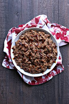 Instant pot pulled pork in a white bowl on top of red and white napkins on a dark wood surface.