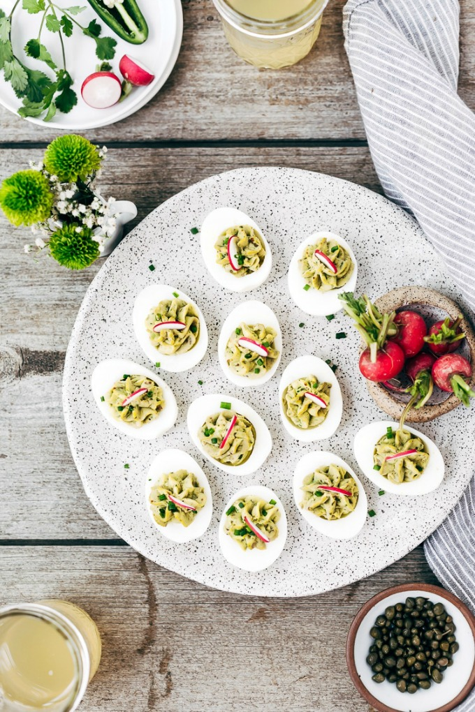 overhead image of a tablescape featuring Avocado Deviled Eggs Without Mayo from Foolproof Living