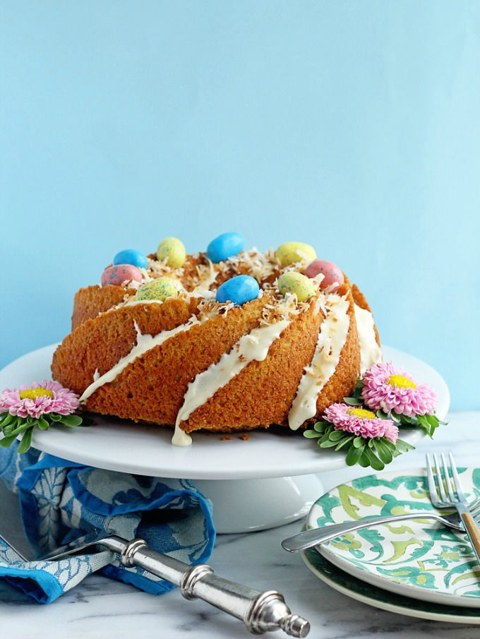 front view of an Easy Carrot Cake Pound Cake from Grandbaby Cakes on a white cake stand against a blue background
