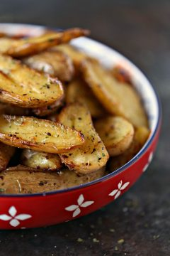 roasted lemon roasted fingerling potatoes served in a red bowl