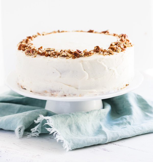 image of Classic Carrot Layer Cake with Cream Cheese Frosting from Spoonful of Flavor on a white cake stand