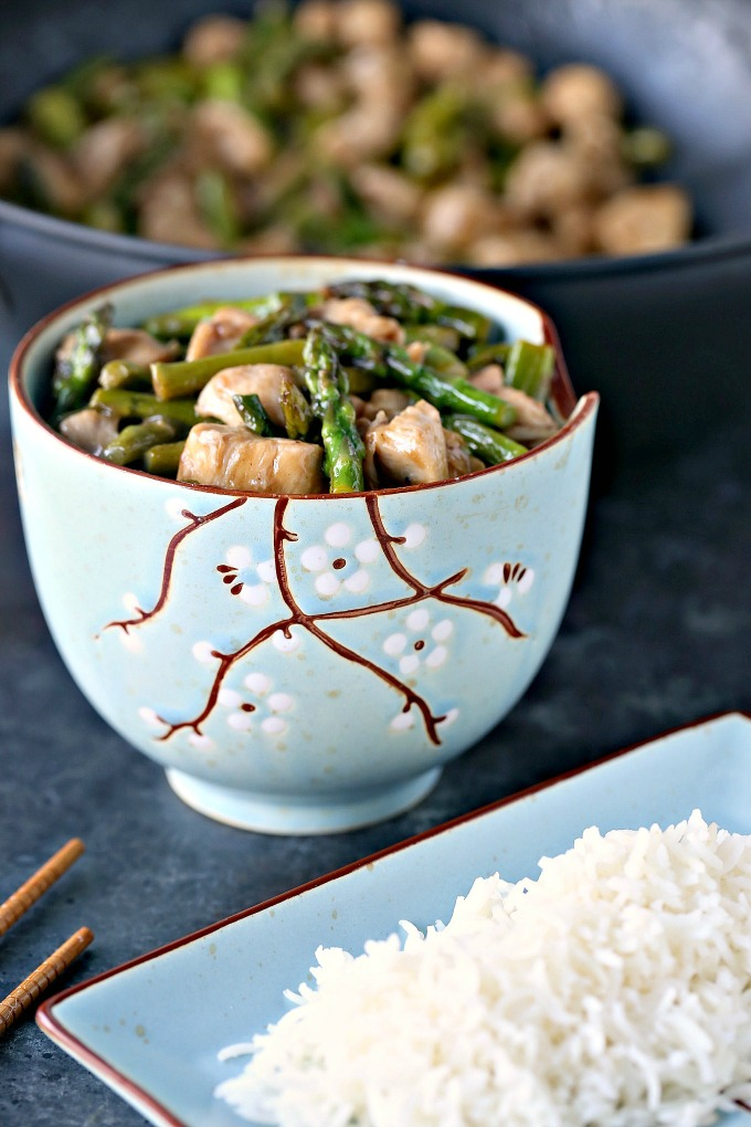 Chicken and Asparagus Stir-Fry with Lemon served in a blue stir fry bowl with white rice on a blue serving plate