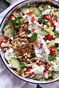 overhead image of Greek chicken orzo power bowls on a white napkin