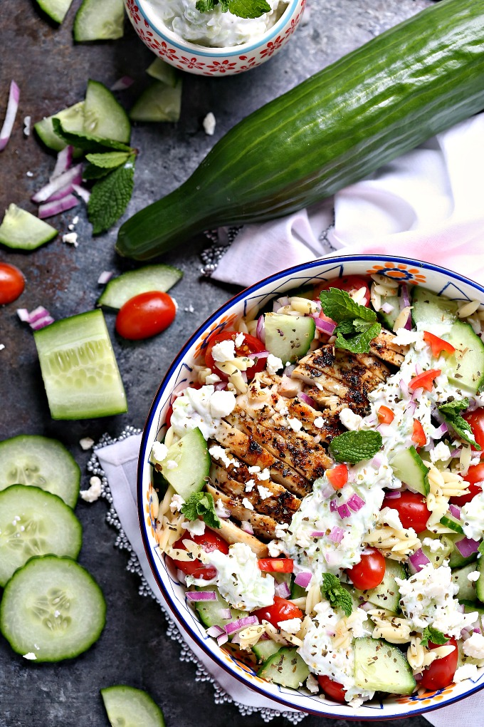 overhead image of Greek chicken orzo power bowls with ingredients scattered on tabletop